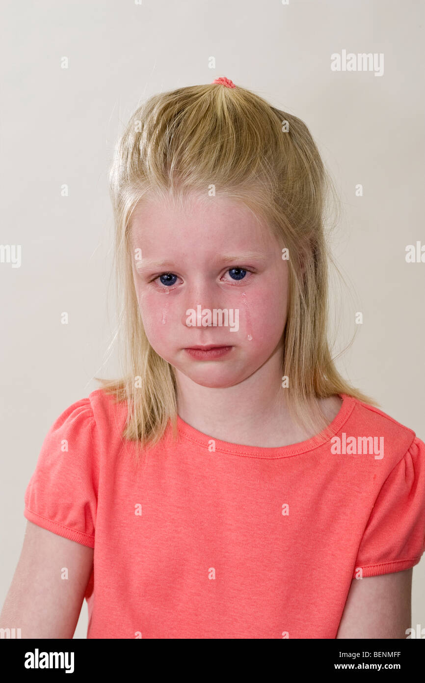 Caucasian 6 year old girl crying with deep sadness abandonment abandoned crushed facial expression deeply felt  - Stock Image
