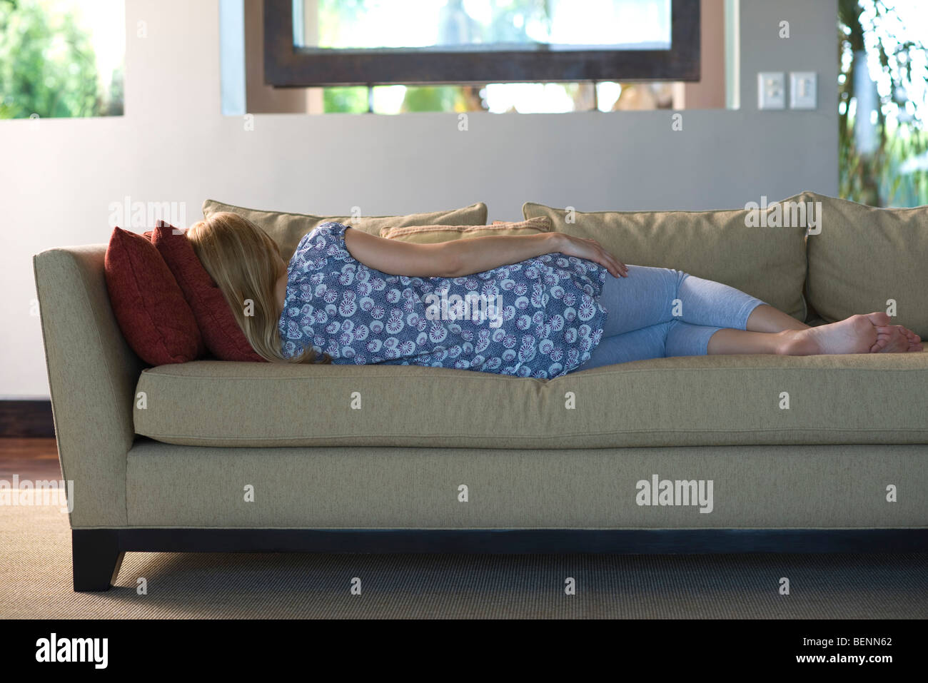 Young woman napping on sofa, rear view - Stock Image
