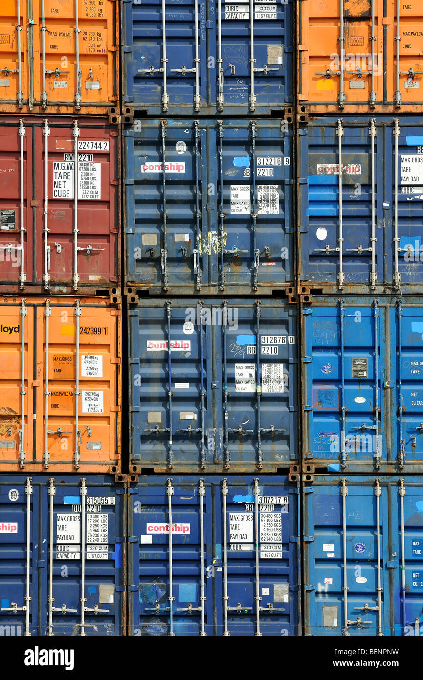 Piled up / Stacked up shipping containers at container terminal in port - Stock Image