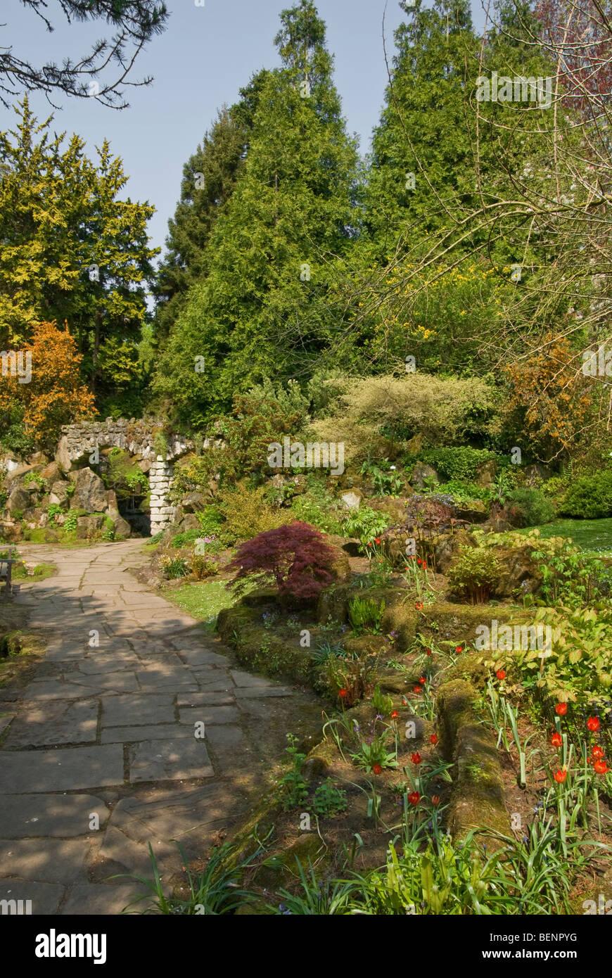 tulips moss ferns stone arch conifers epimedium acer [Newby Hall] Ripon [North Yorkshire] - Stock Image
