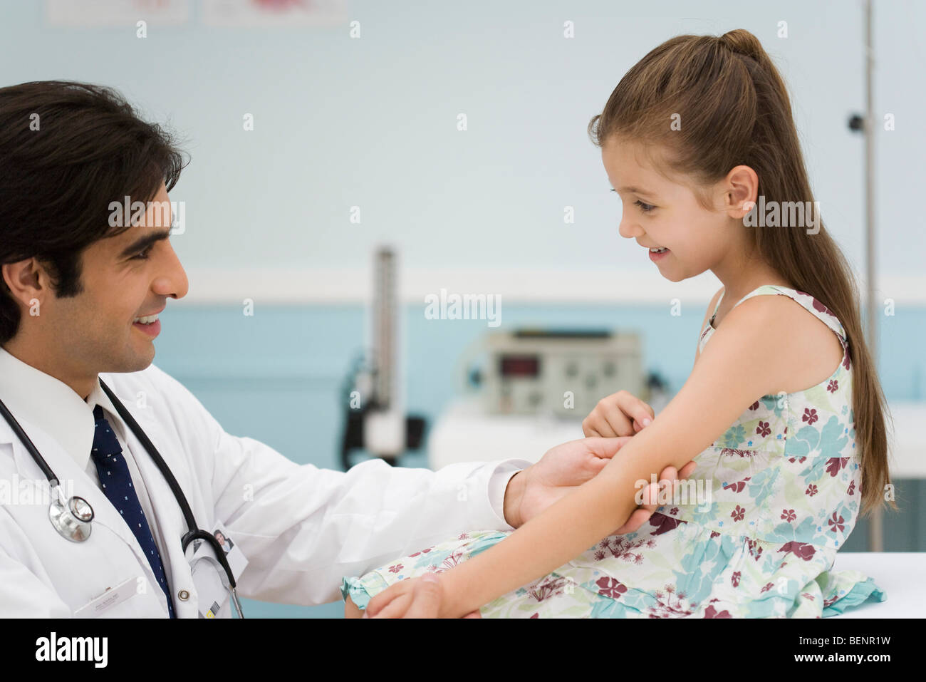 Friendly doctor examining little girl's arm Stock Photo