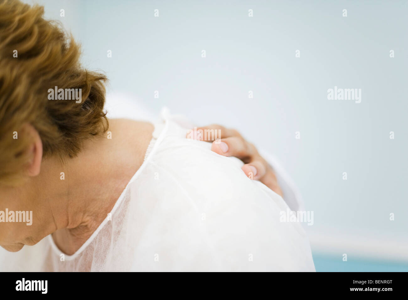 Patient being consoled by doctor, head down, cropped - Stock Image