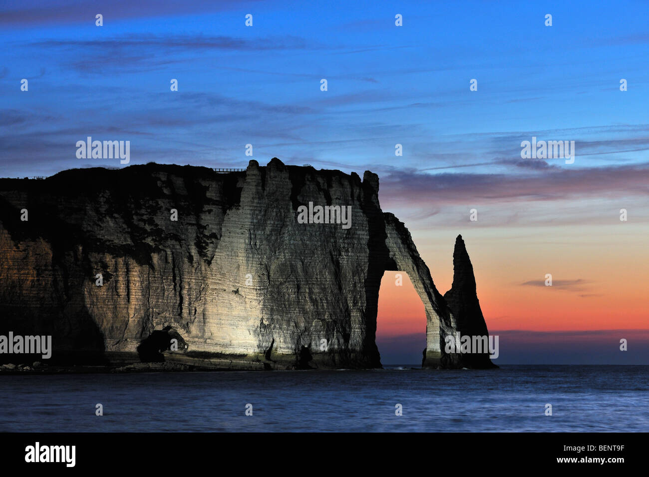 L'Aiguille and The Porte d'Aval at sunset, a natural arch at Etretat which is illuminated artificially, - Stock Image