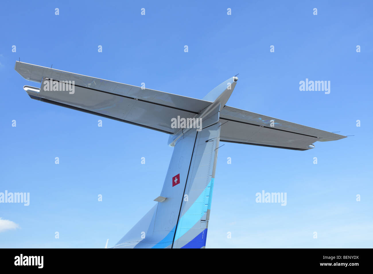 Tail section of light aircraft including rudder, tail-wings and elevators set against a blue sky background. - Stock Image