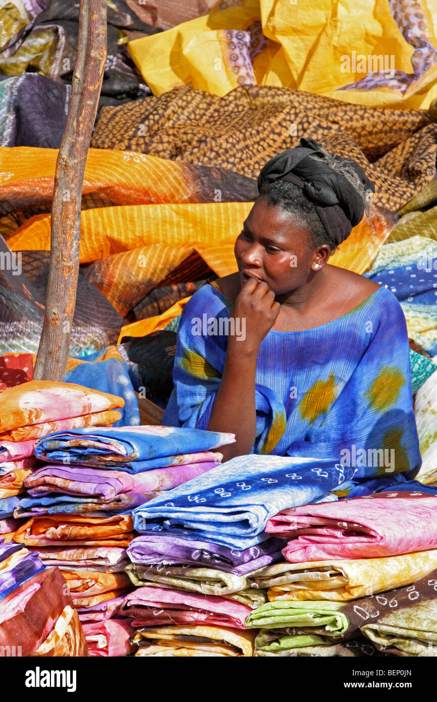 Black woman in traditional clothing selling colourful cloths on market in Nouakchott / Nouakshott, Mauritania, Africa - Stock Image
