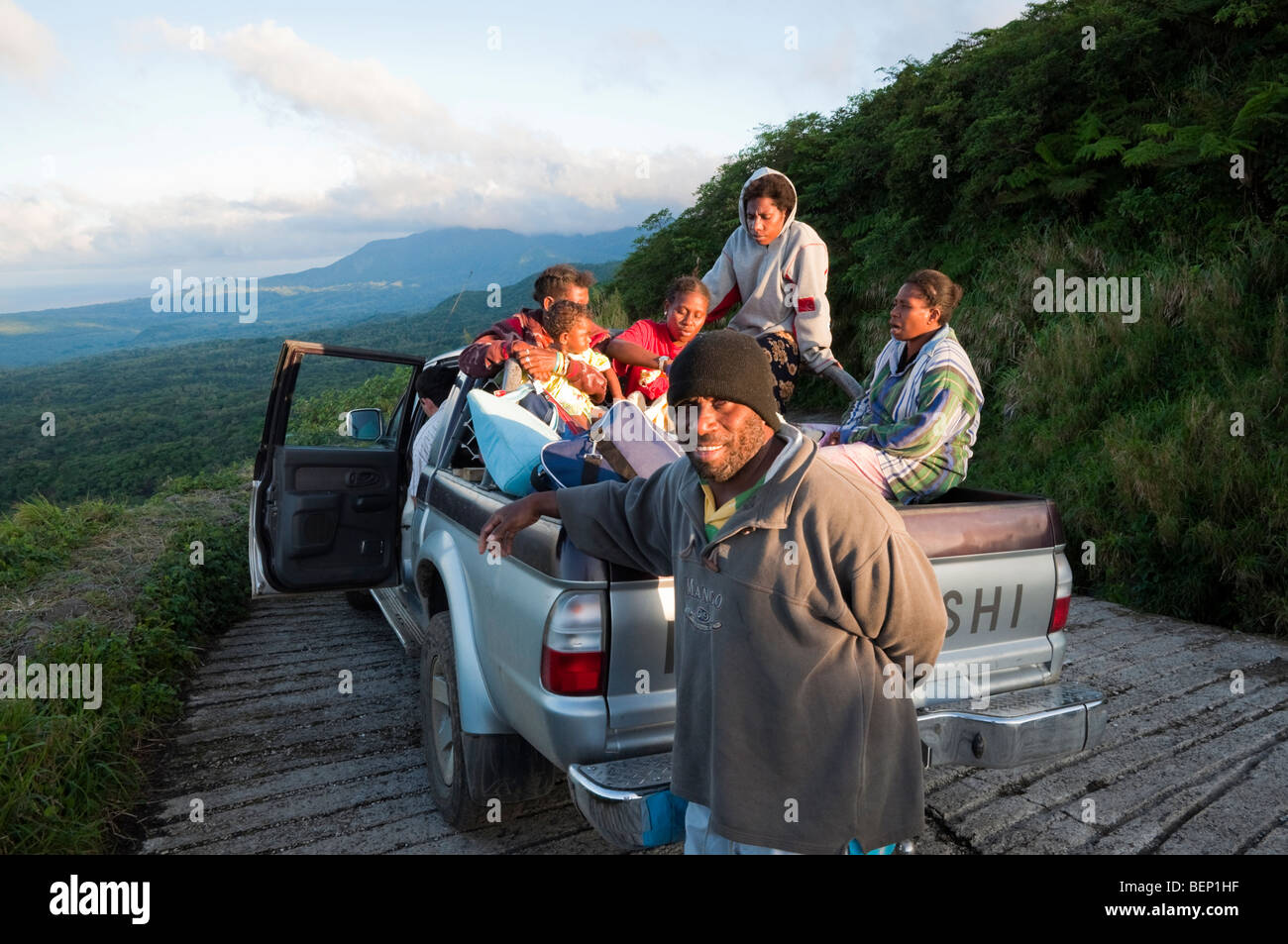 Developing country transport: a family and other villagers in the back of a pickup truck - Stock Image