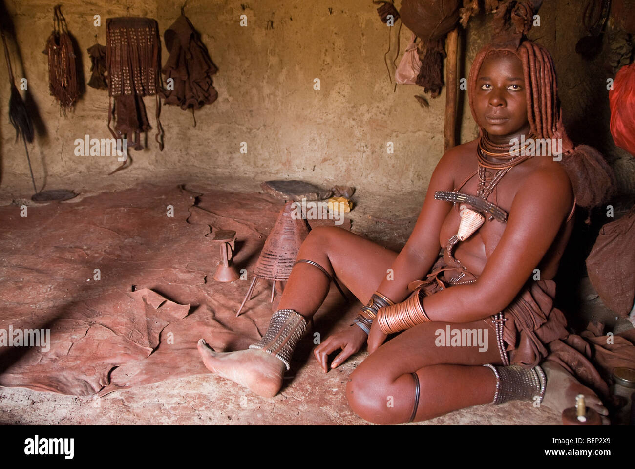Himba woman in her hut in a village near Epupa Falls, Namibia, Africa. - Stock Image