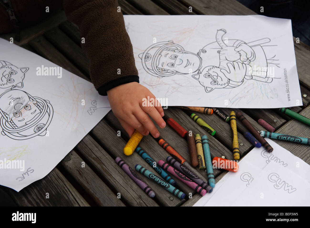 A young child colouring in a picture of Fireman Sam at a pre school ...