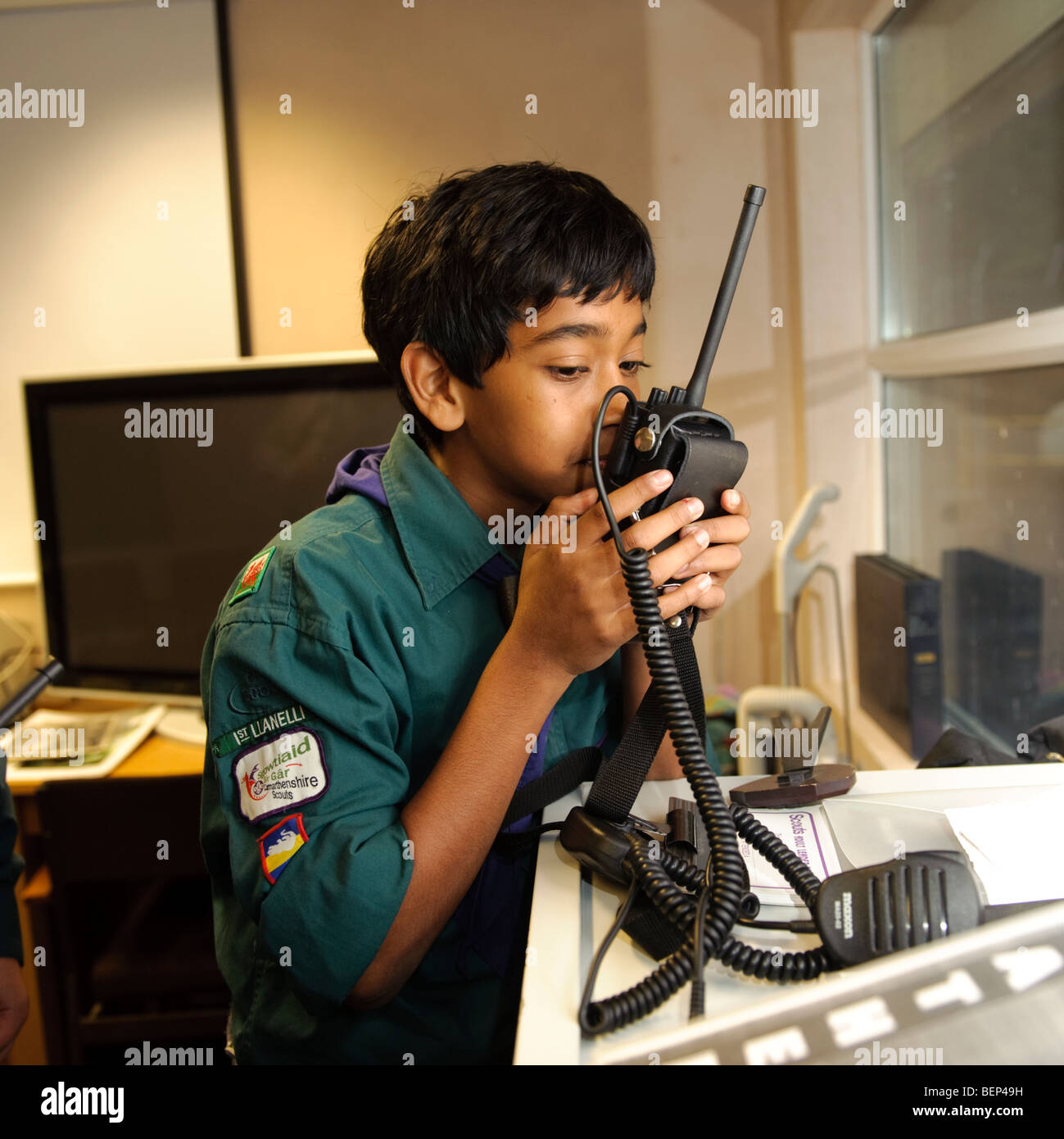 An ethnic minority  Boy Scout using walkie-talkie in the clubhouse UK - Stock Image