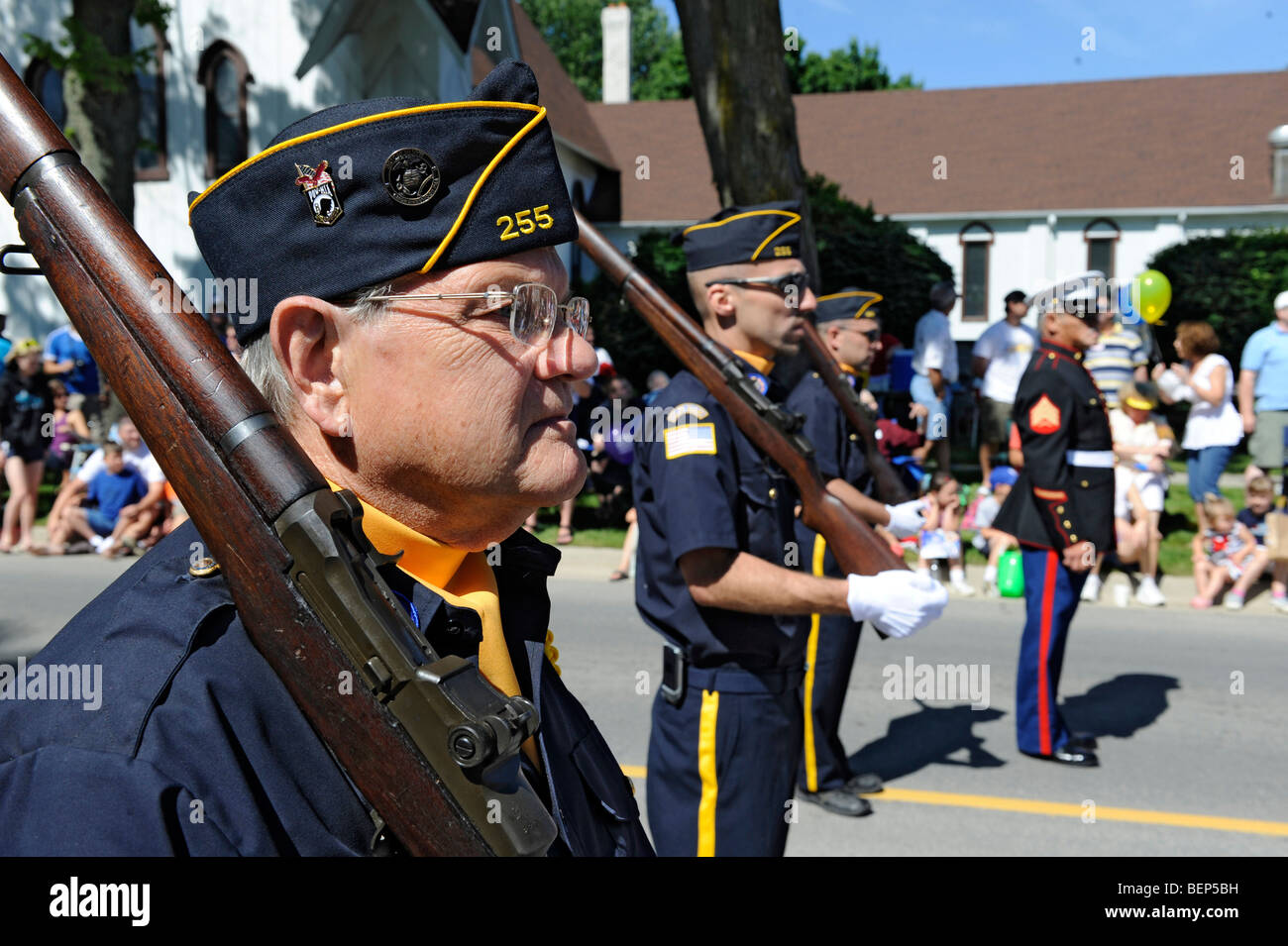 Uniformed Veterans Marching in Parade Honor Guard with Flags Stock Photo