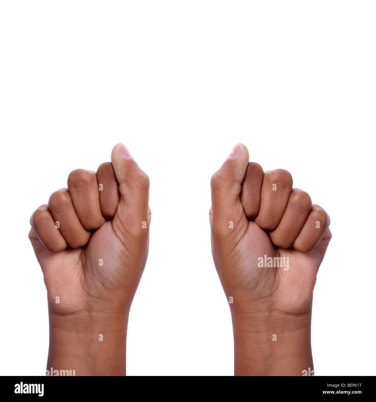 young dark skinned mixed race girls hands making fists as if to hide something, includes clipping path isolated - Stock Image
