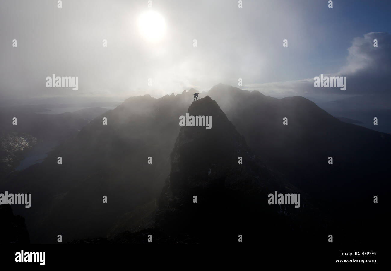 A lone climber stands on a mountain summit in the Black Cuillins, with a mist shrouded sun behind him, Isle of Skye, - Stock Image