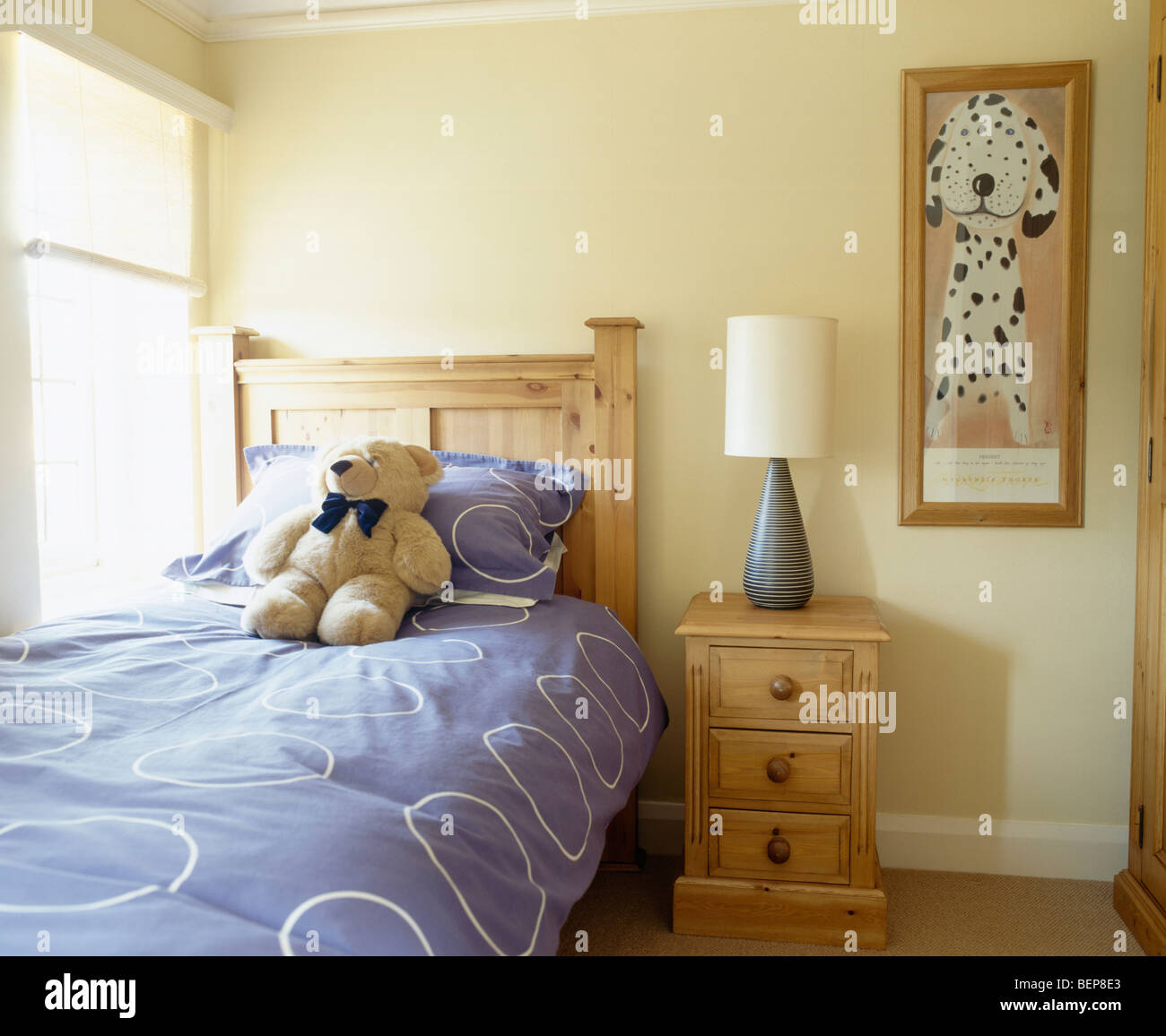 Teddy-bear and blue quilt on pine bed in child\'s cream ...