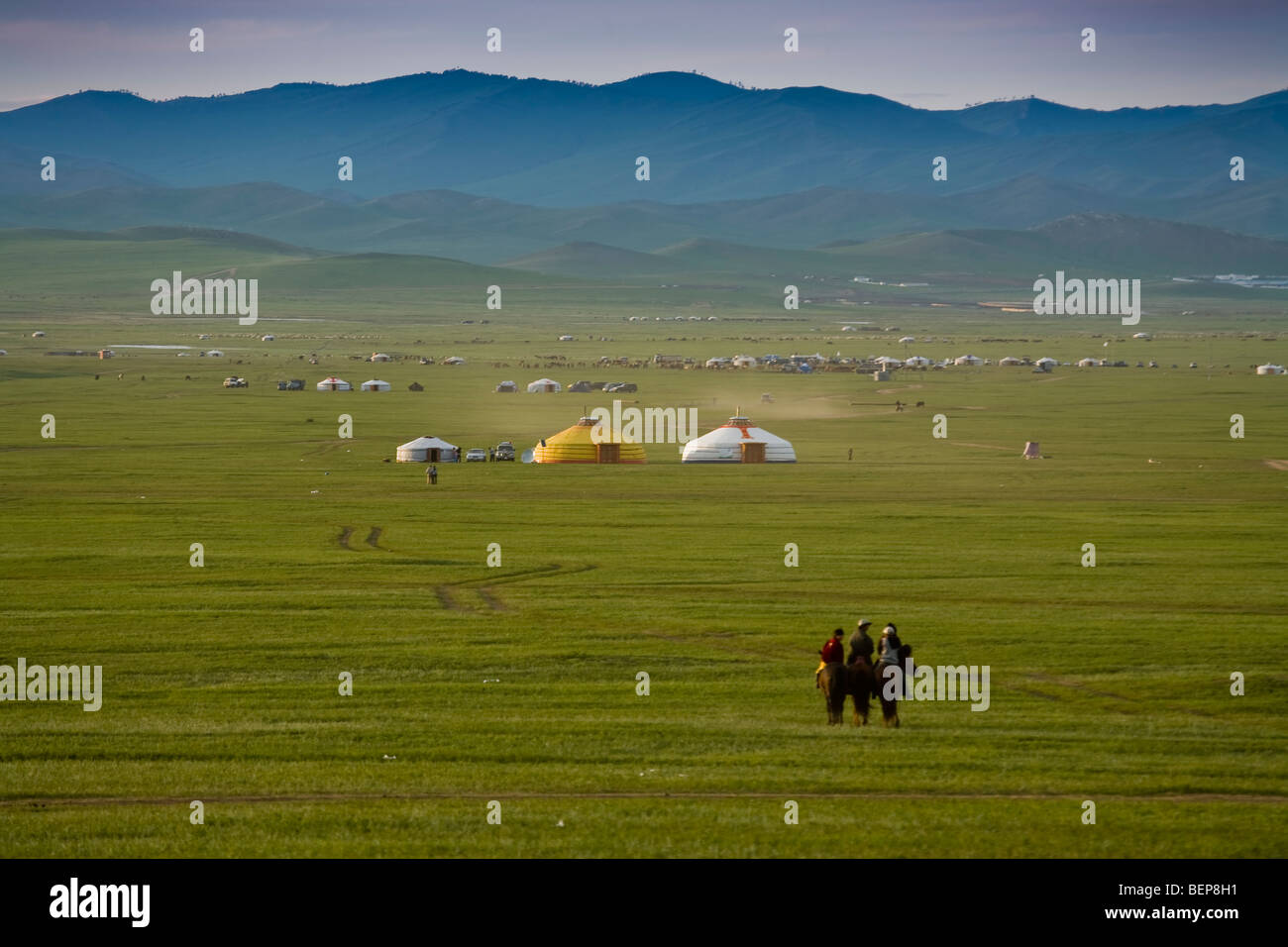 Mongolian Kids riding horses home on a sunny afternoon on the steppe - Stock Image