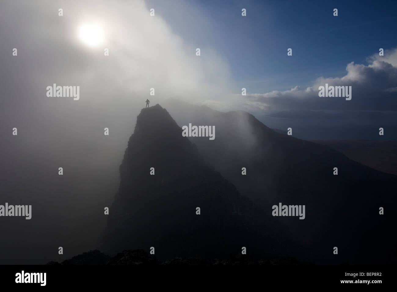 A lone climber stands on a mountain summit in the Black Cuillins, with a mist shrouded sun behind him. Isle of Skye, - Stock Image