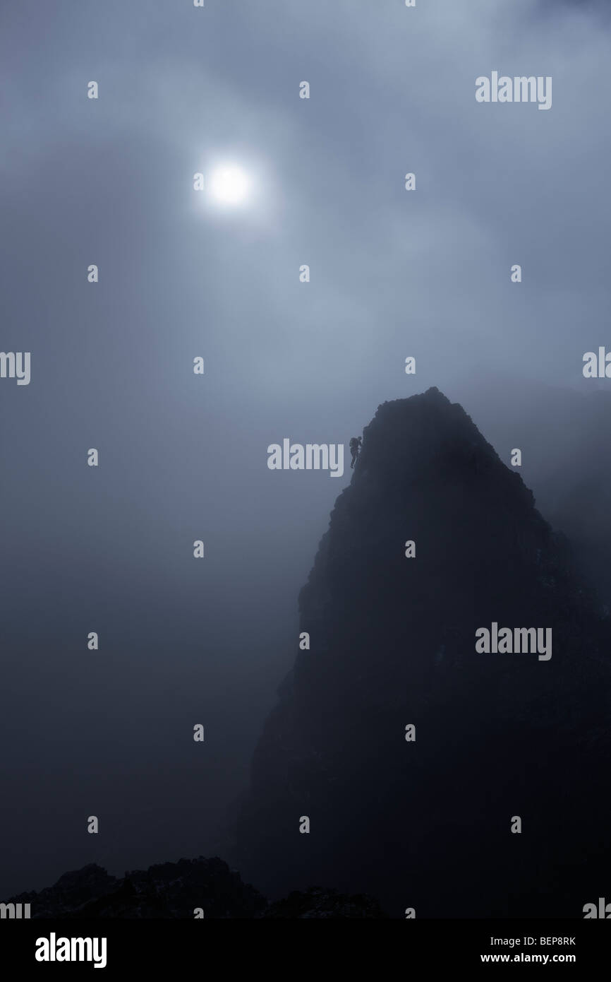 A lone climber scales a steep mountain summit in the Black Cuillins, with a mist shrouded sun behind him, Isle of - Stock Image
