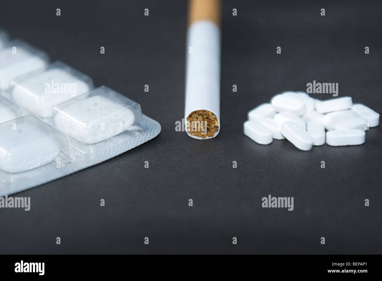 A cigarette, nicotine gum and anti-smoking pills on a black background. Different options for quitting smoking. - Stock Image