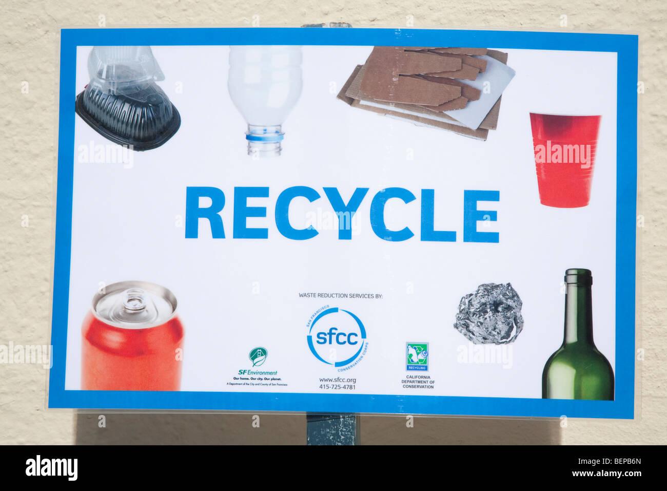 'Recycle' recycling sign showing recyclable materials - aluminum cans, glass bottles, plastic bottles, cardboard, - Stock Image