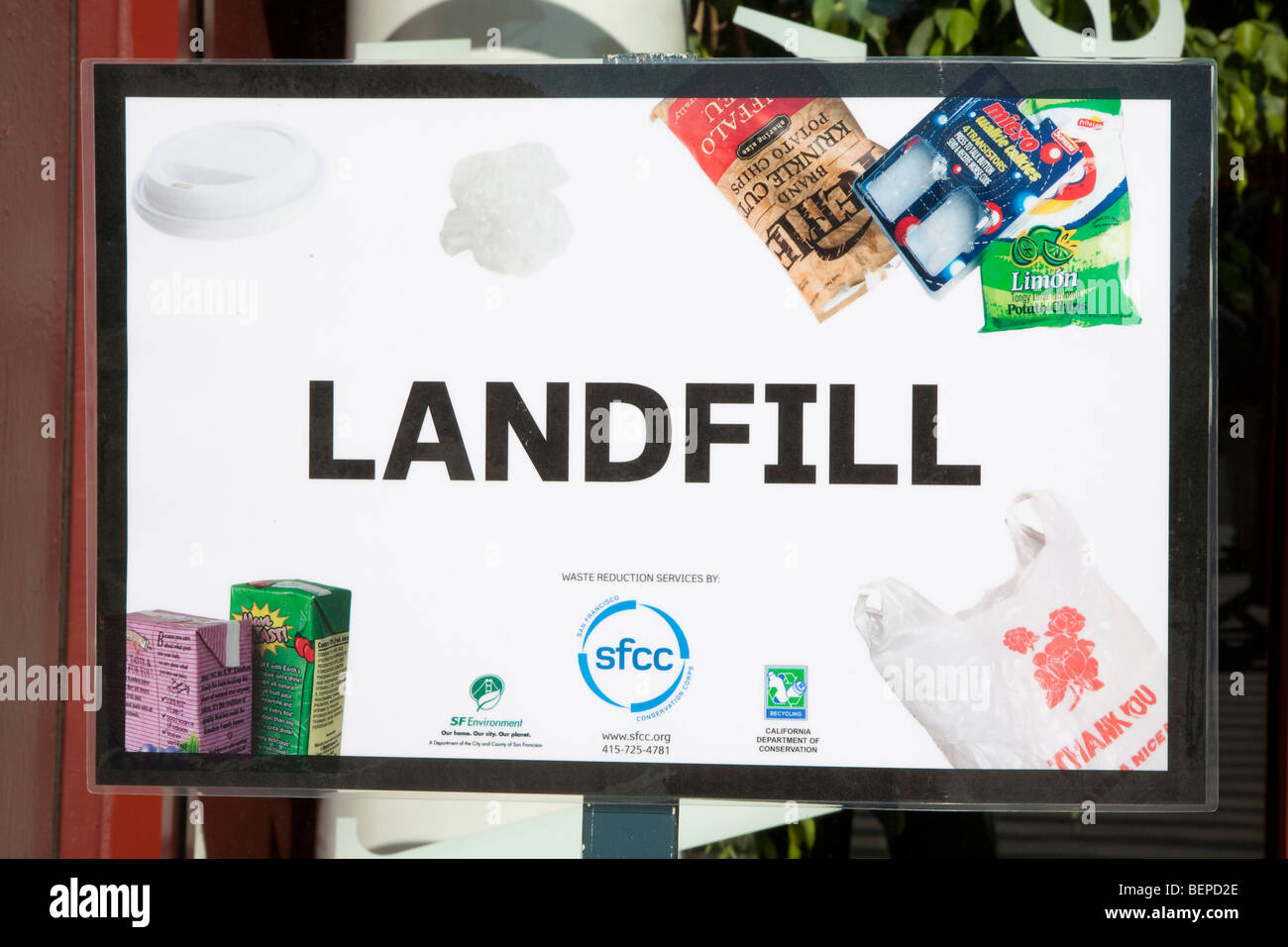 'Landfill' garbage sign showing non-recyclable materials - juice paks, potato chip bags, plastic bags, plastic - Stock Image