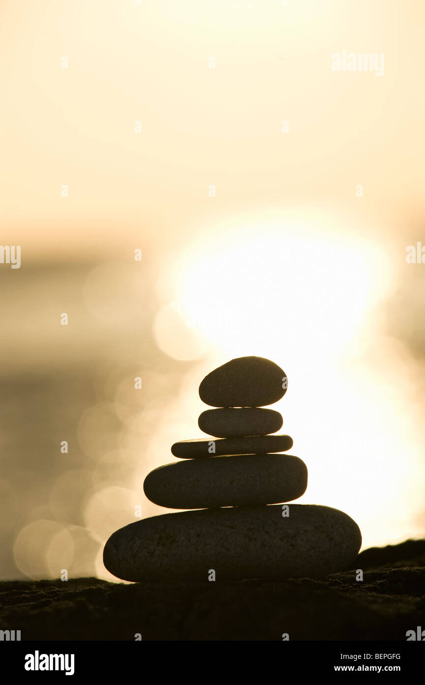 A stone stack against a setting sun - Stock Image