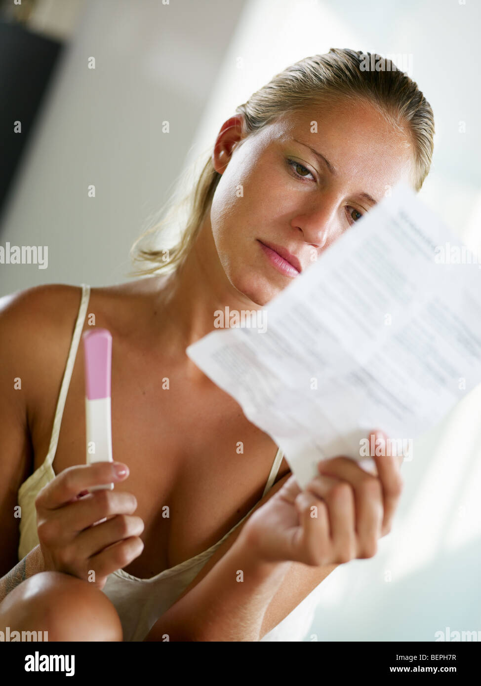 blonde woman holding pregnancy test and reading information. Stock Photo
