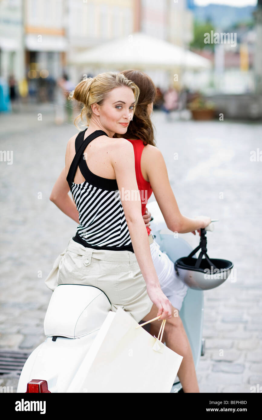 girlfriends on a motor scooter Stock Photo