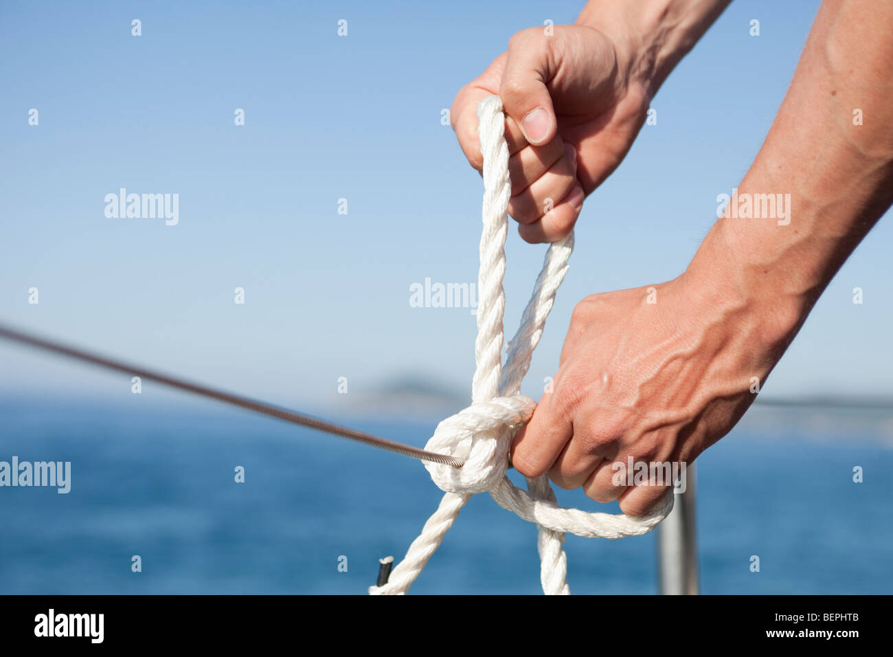 man making knot into rope - Stock Image
