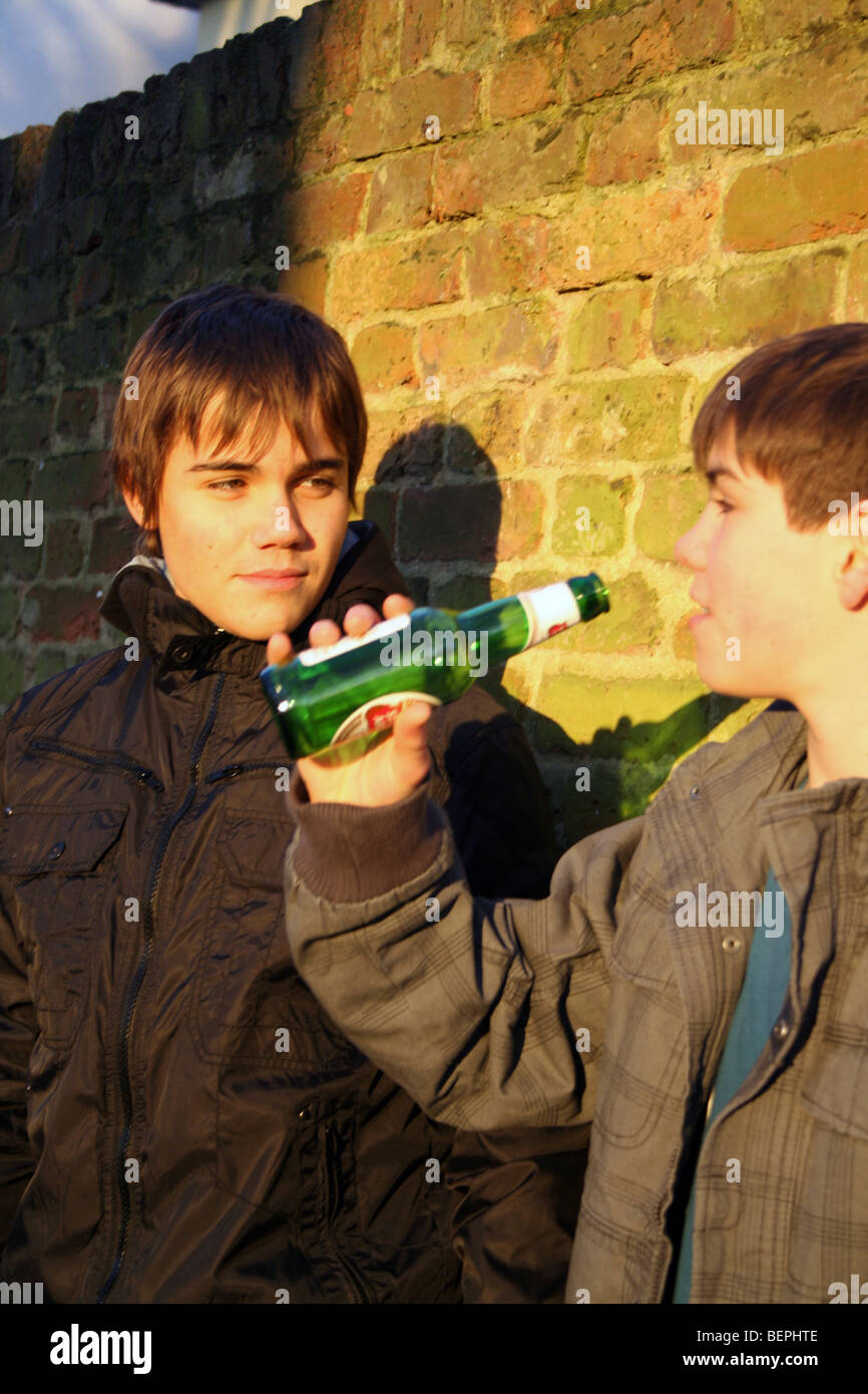 Two underage boys sharing a beer - Stock Image