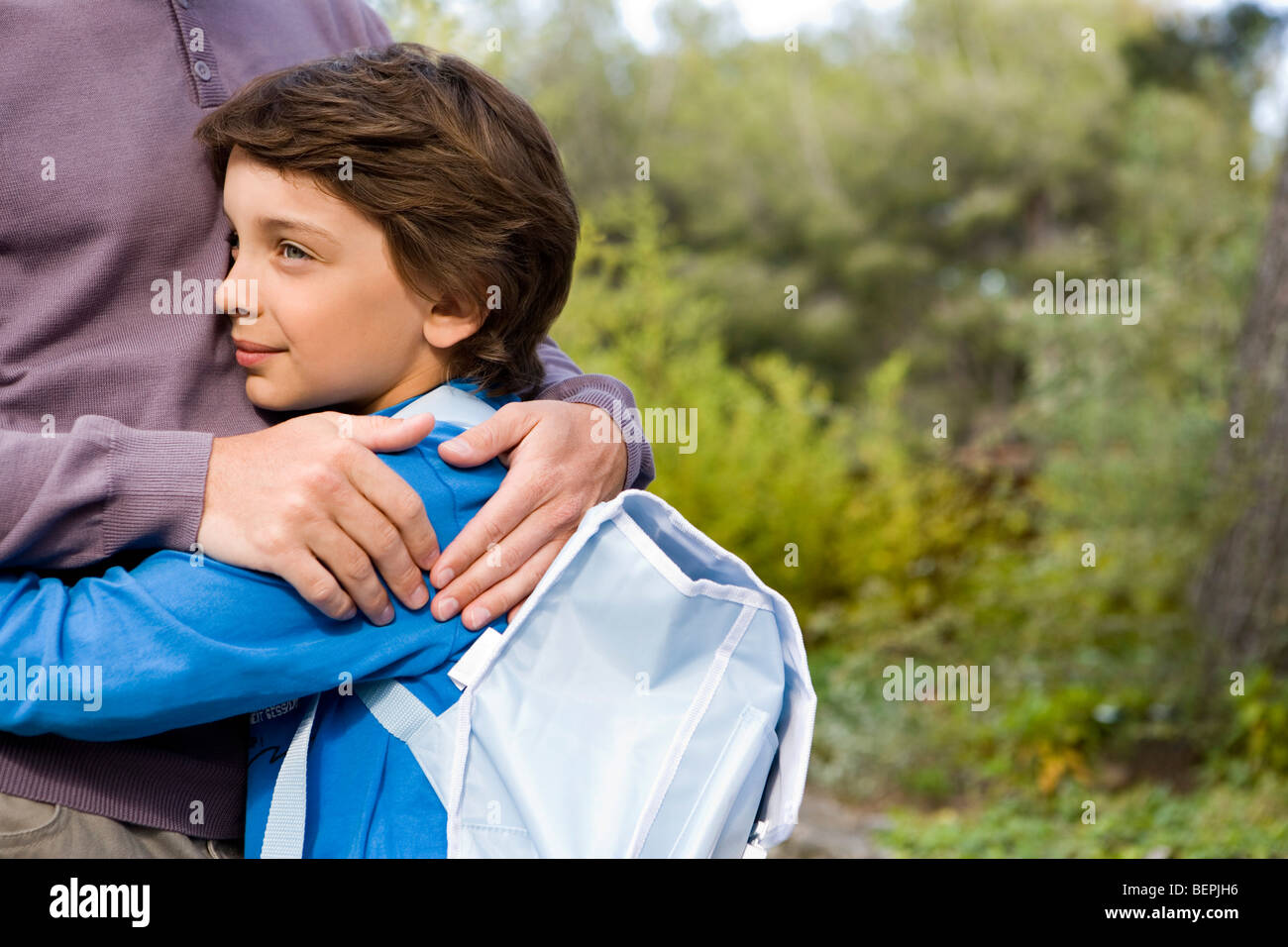 boy cuddling dad back from school - Stock Image