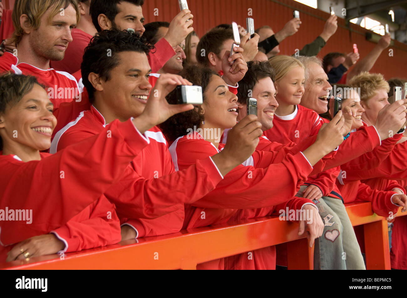 Fans taking photographs at football match - Stock Image