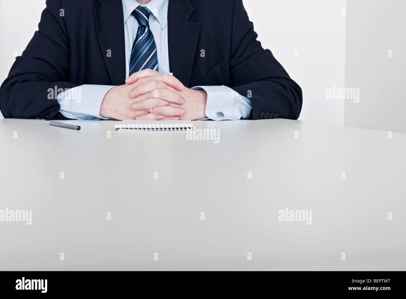 man sitting, hands clasped - Stock Image