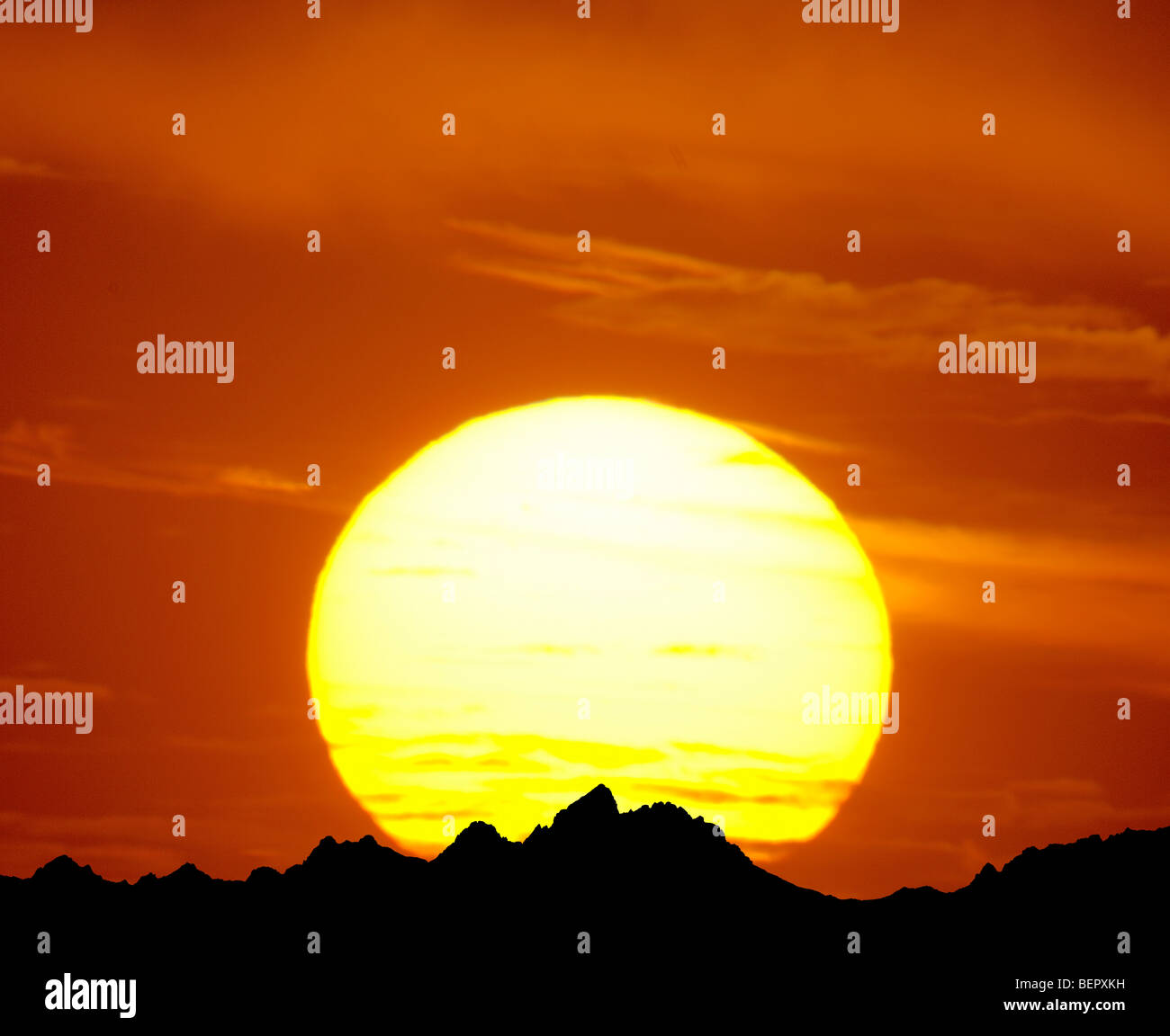 telephoto photograph of large sunset and rocky mountains - Stock Image