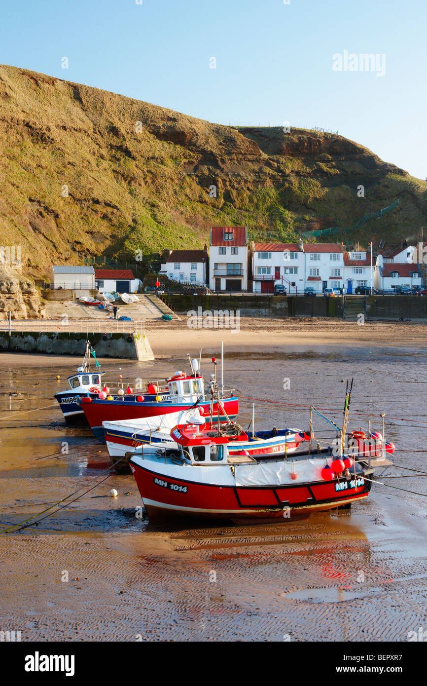 Fishing boats at low tide in Staithes village on the North Yorkshire coast - Stock Image