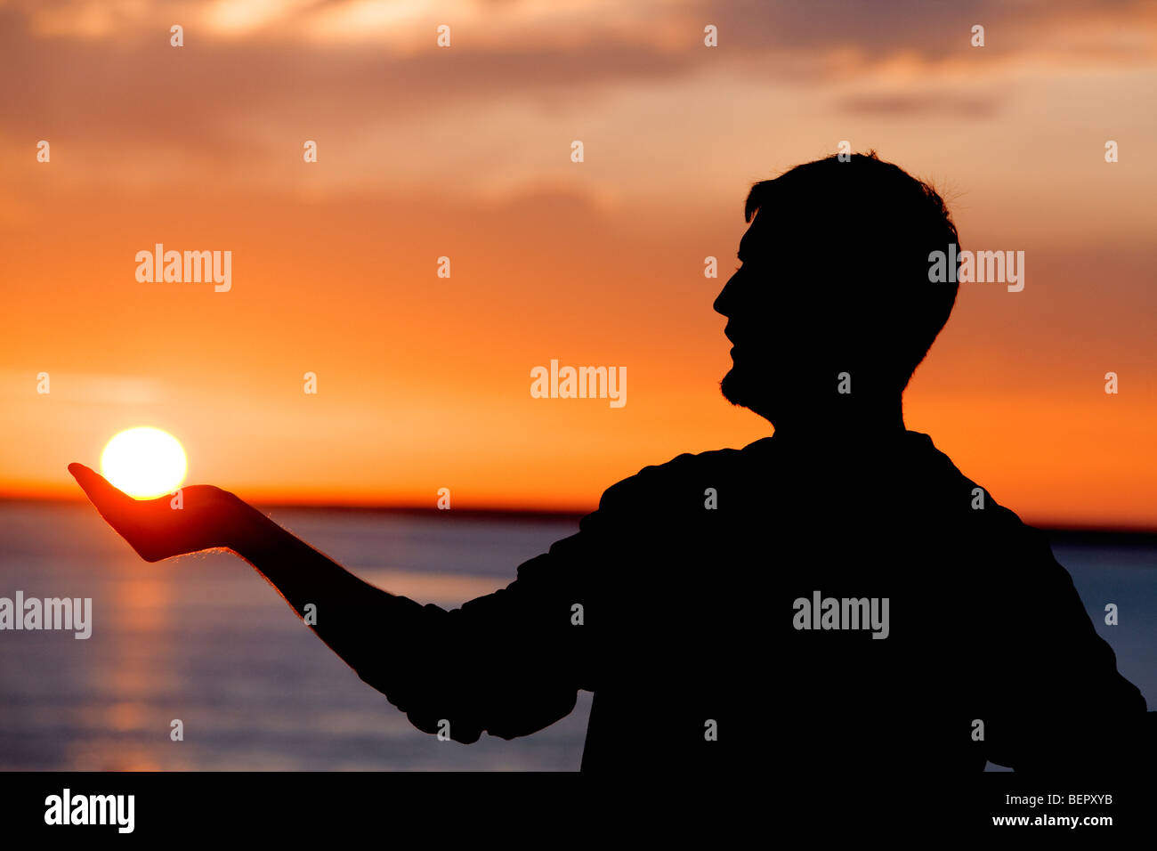 Man holding the sun. - Stock Image