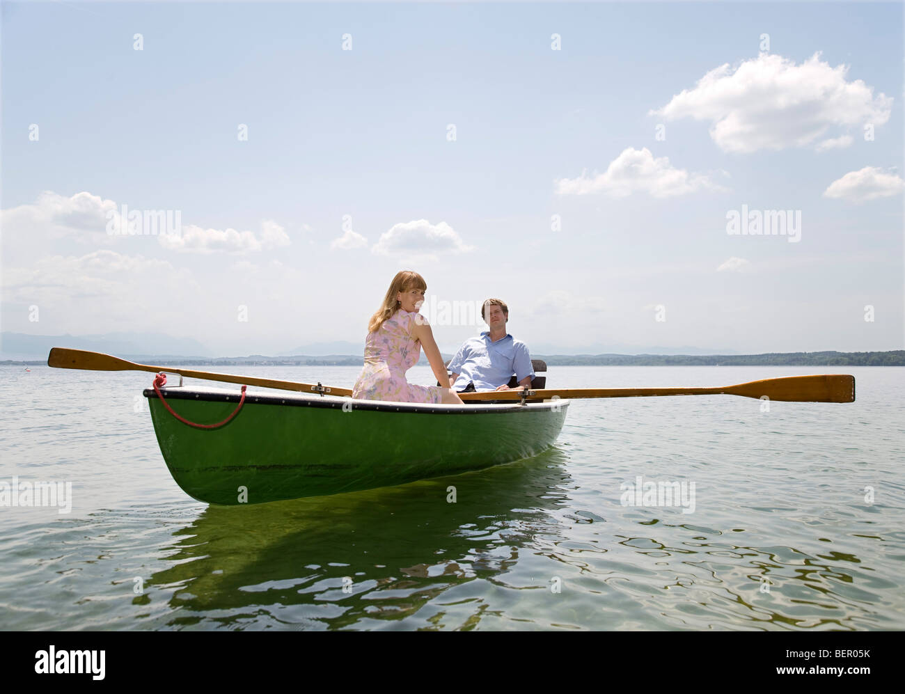 woman and man rowing boat on lake - Stock Image
