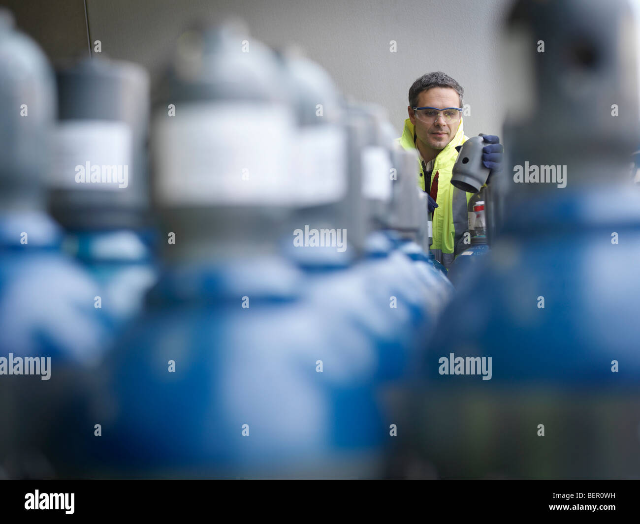 Port Worker Inspecting Gas Canisters - Stock Image