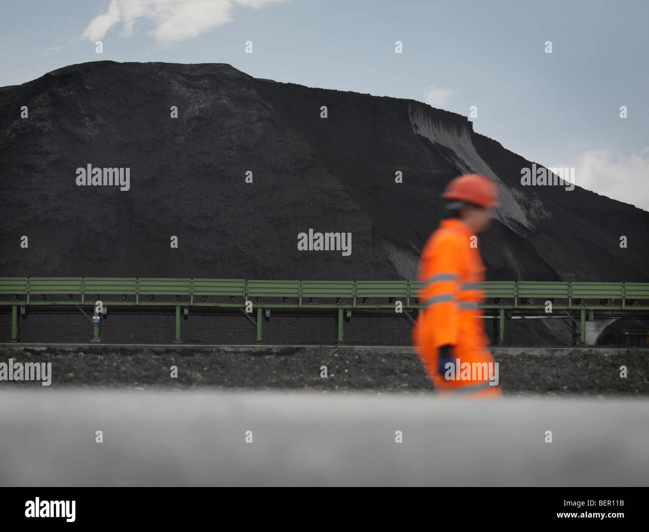 Port Worker With Mound Of Coal - Stock Image