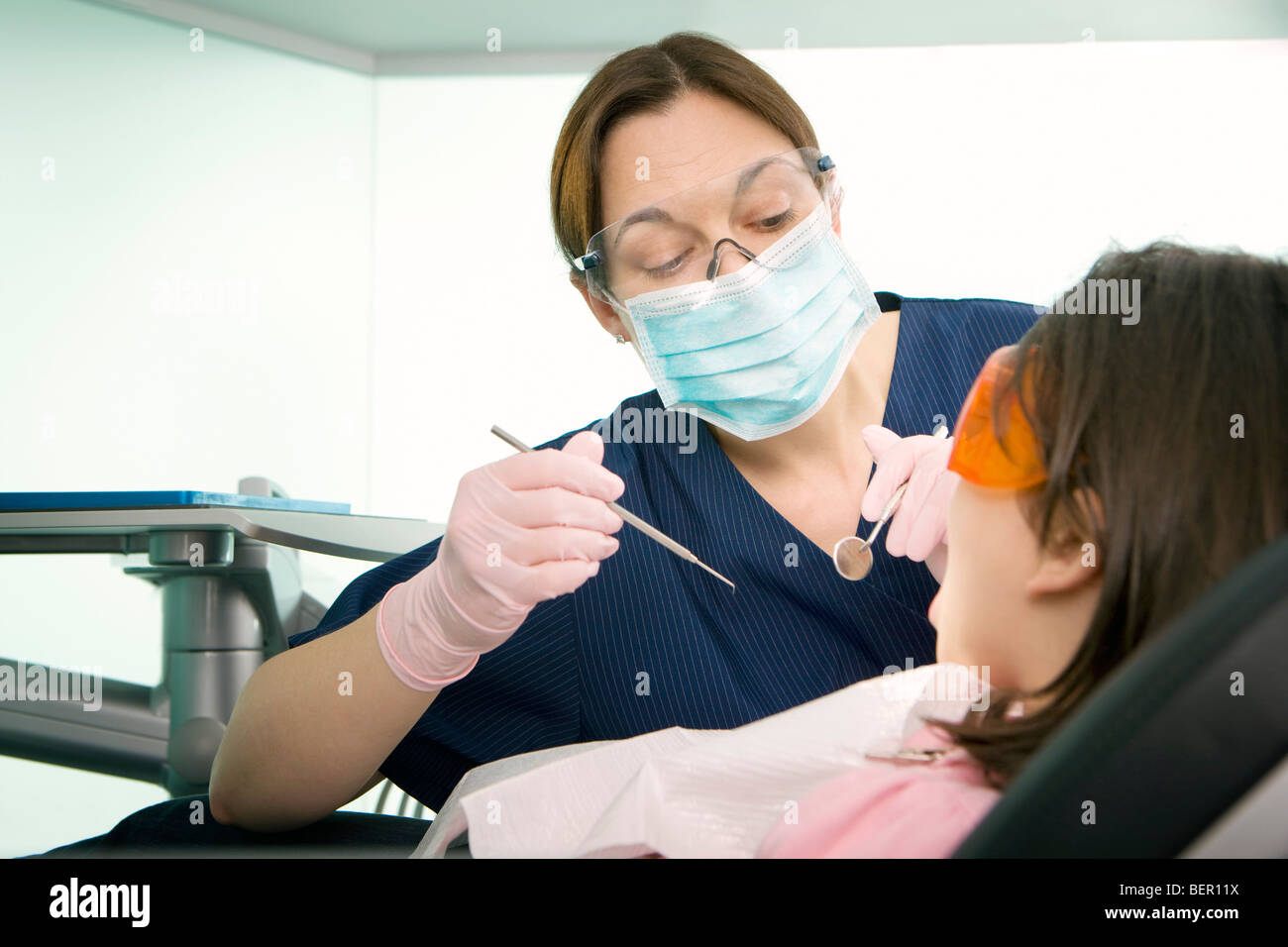 A female dentist treating a patient - Stock Image