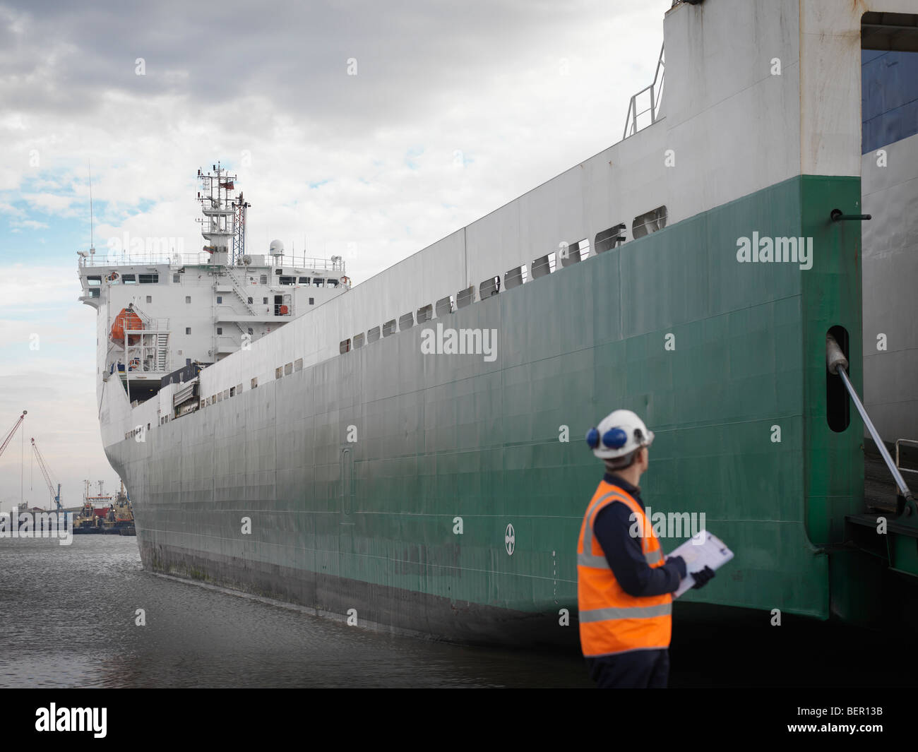 Port Worker Looking At Container Ship - Stock Image