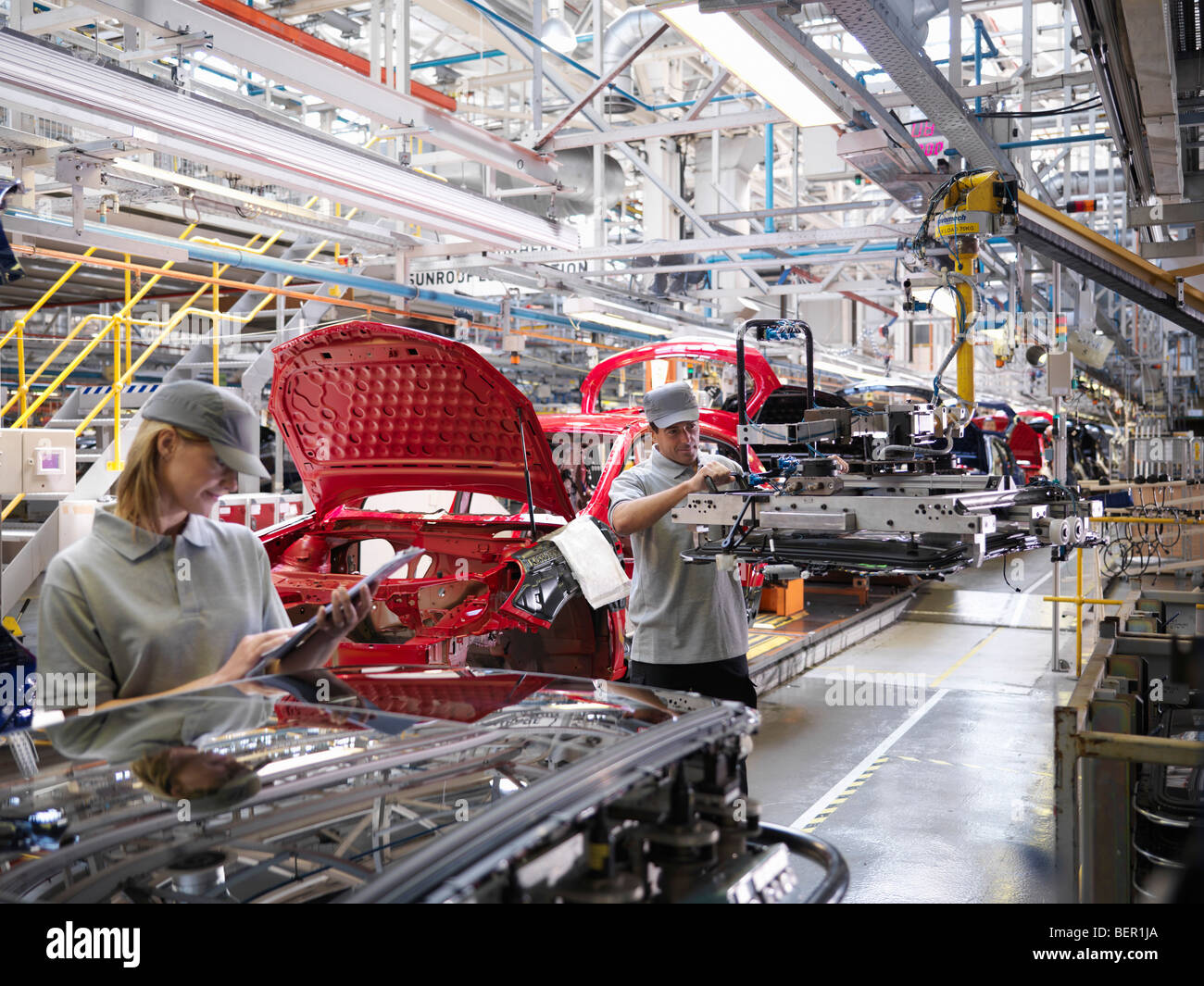 Car Plant Workers On Production Line - Stock Image