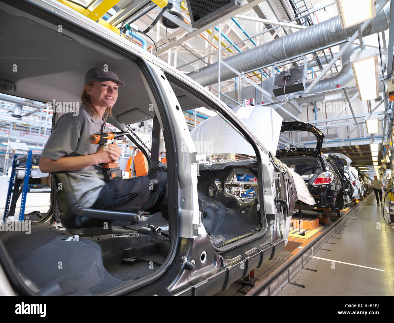 Female Car Worker On Production Line - Stock Image