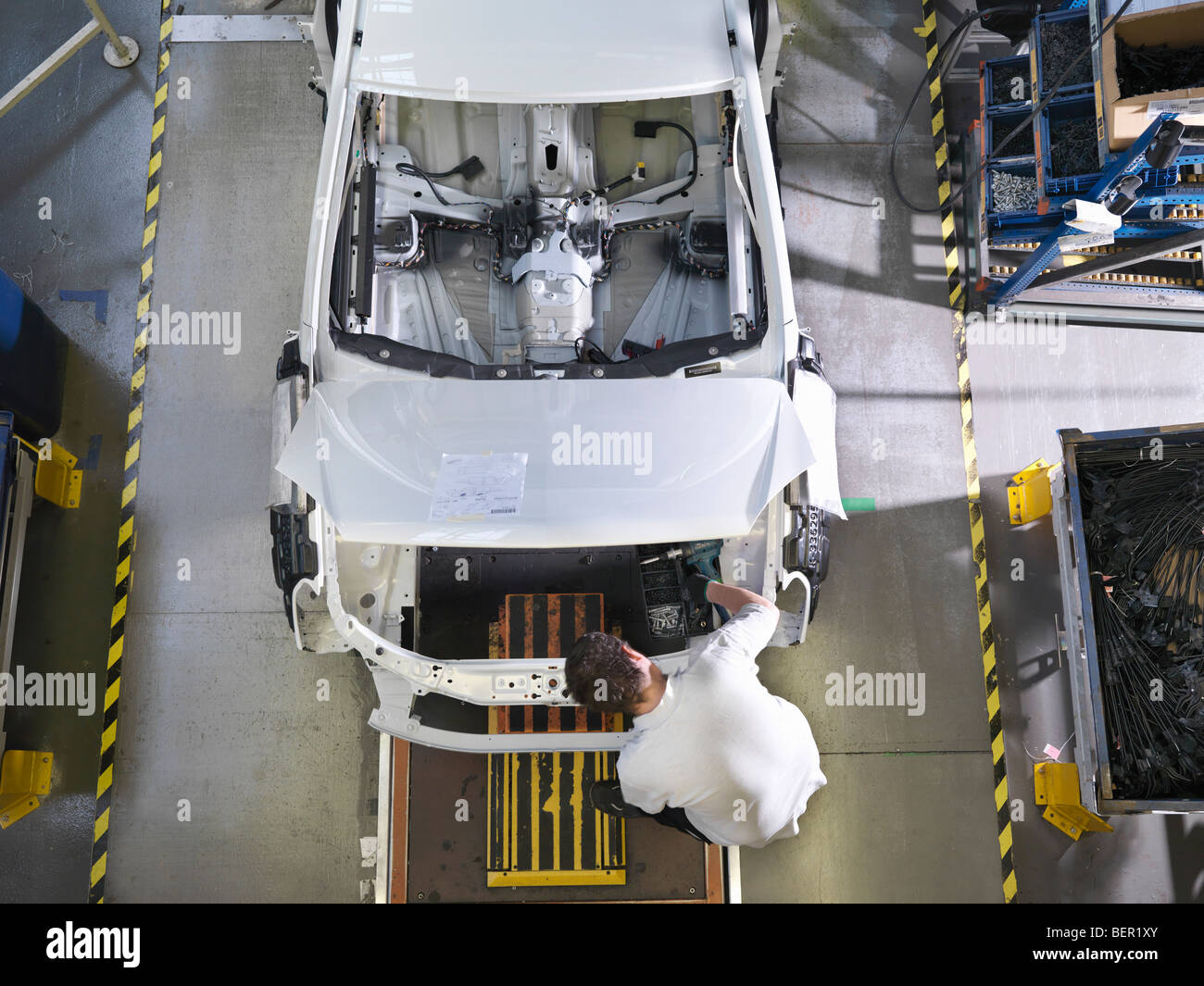 Worker Assembling Car On Production Line - Stock Image
