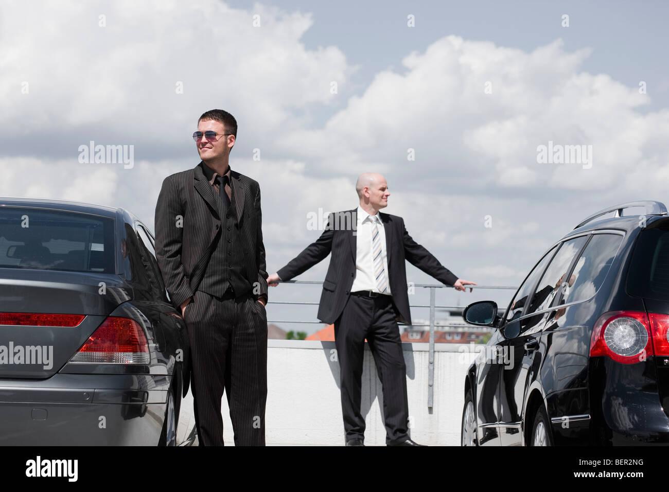 two business men standing between cars - Stock Image