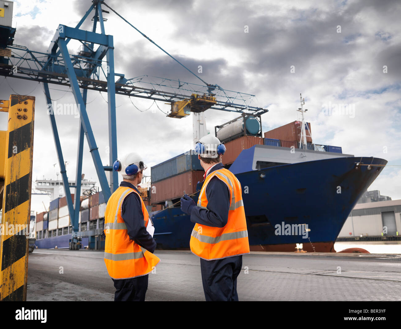 Port Workers With Ship Being Loaded - Stock Image
