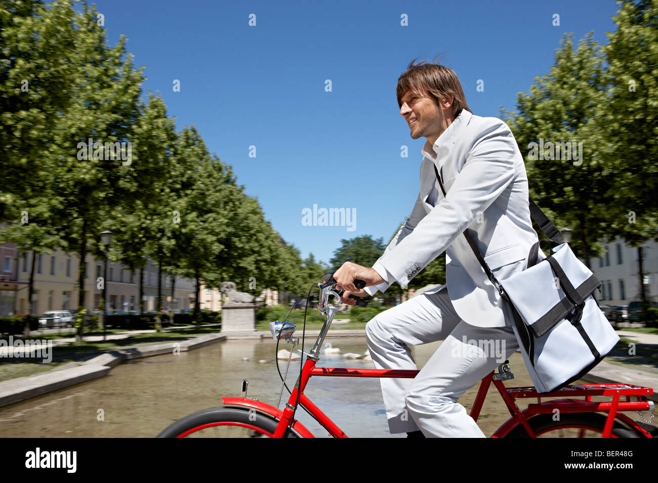 Man bicycling with bag across the city - Stock Image