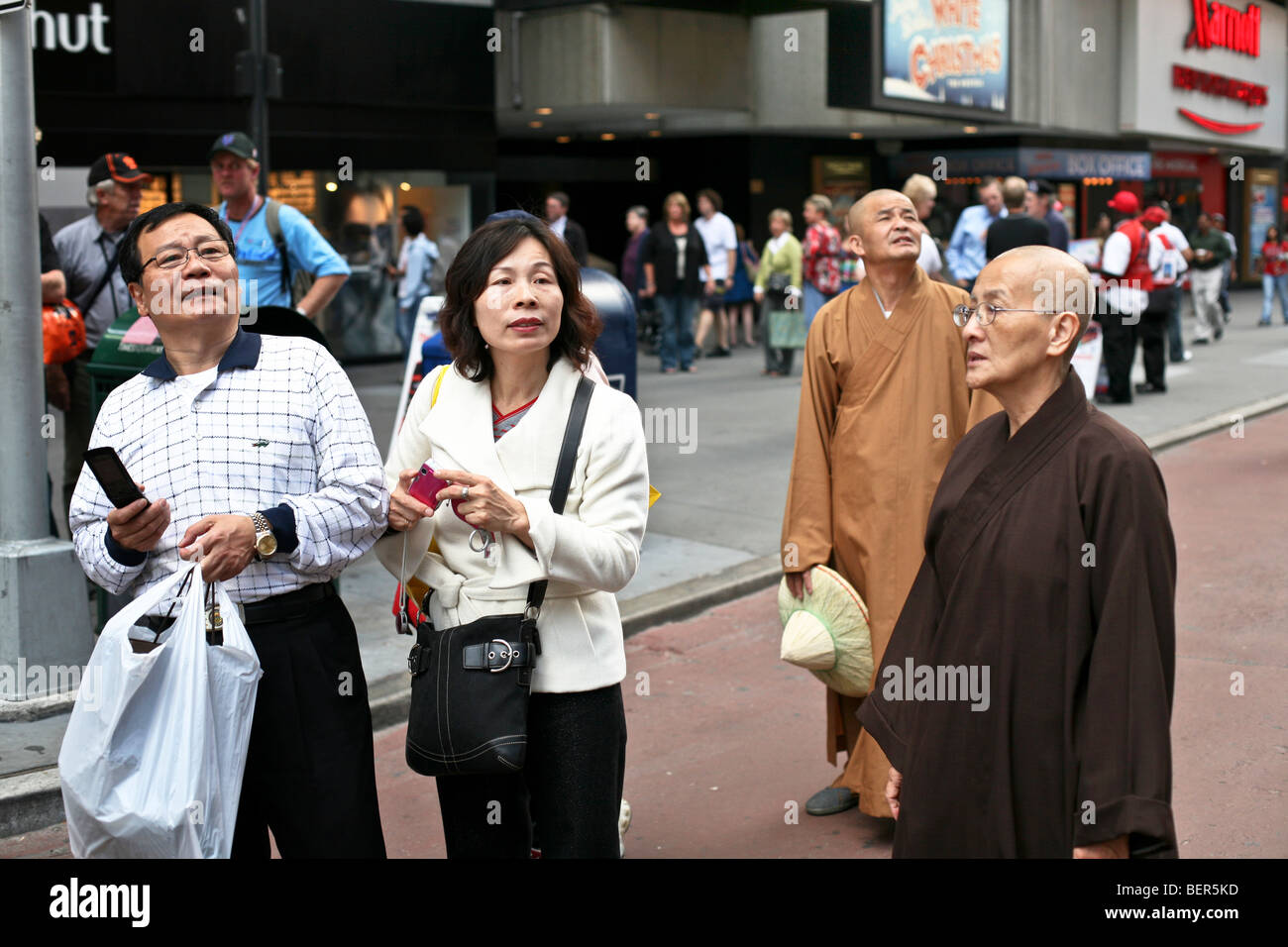 middle aged Japanese tourist couple with two robed Japanese monks in New York City Times Square pedestrian zone - Stock Image
