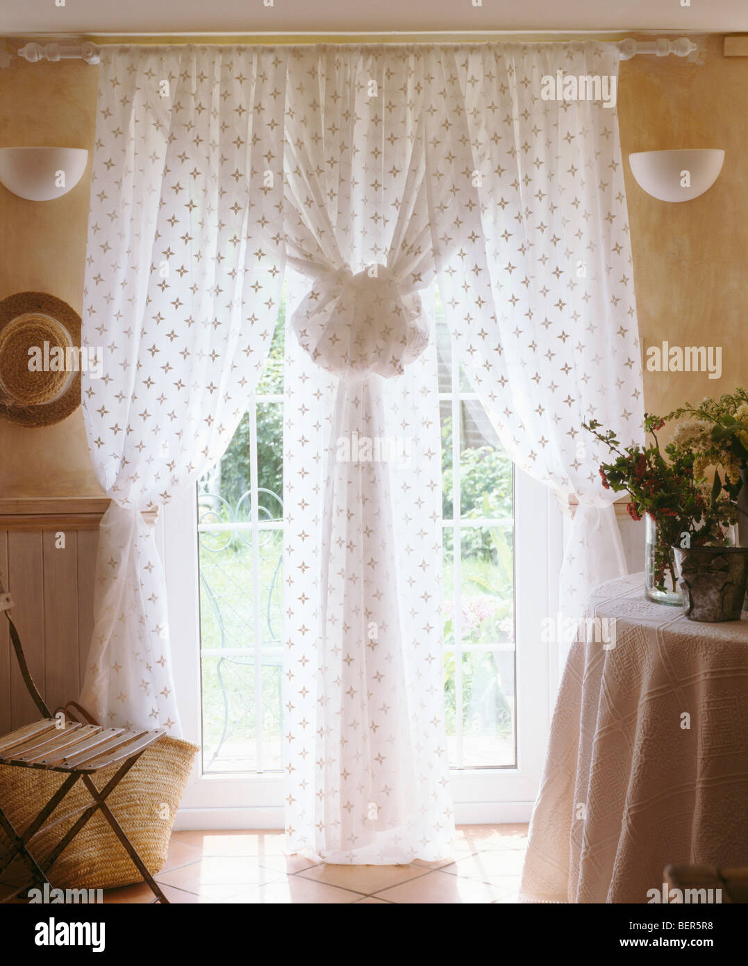 Close-up of patterned white voile curtains at glass doors in cottage living room Stock Photo