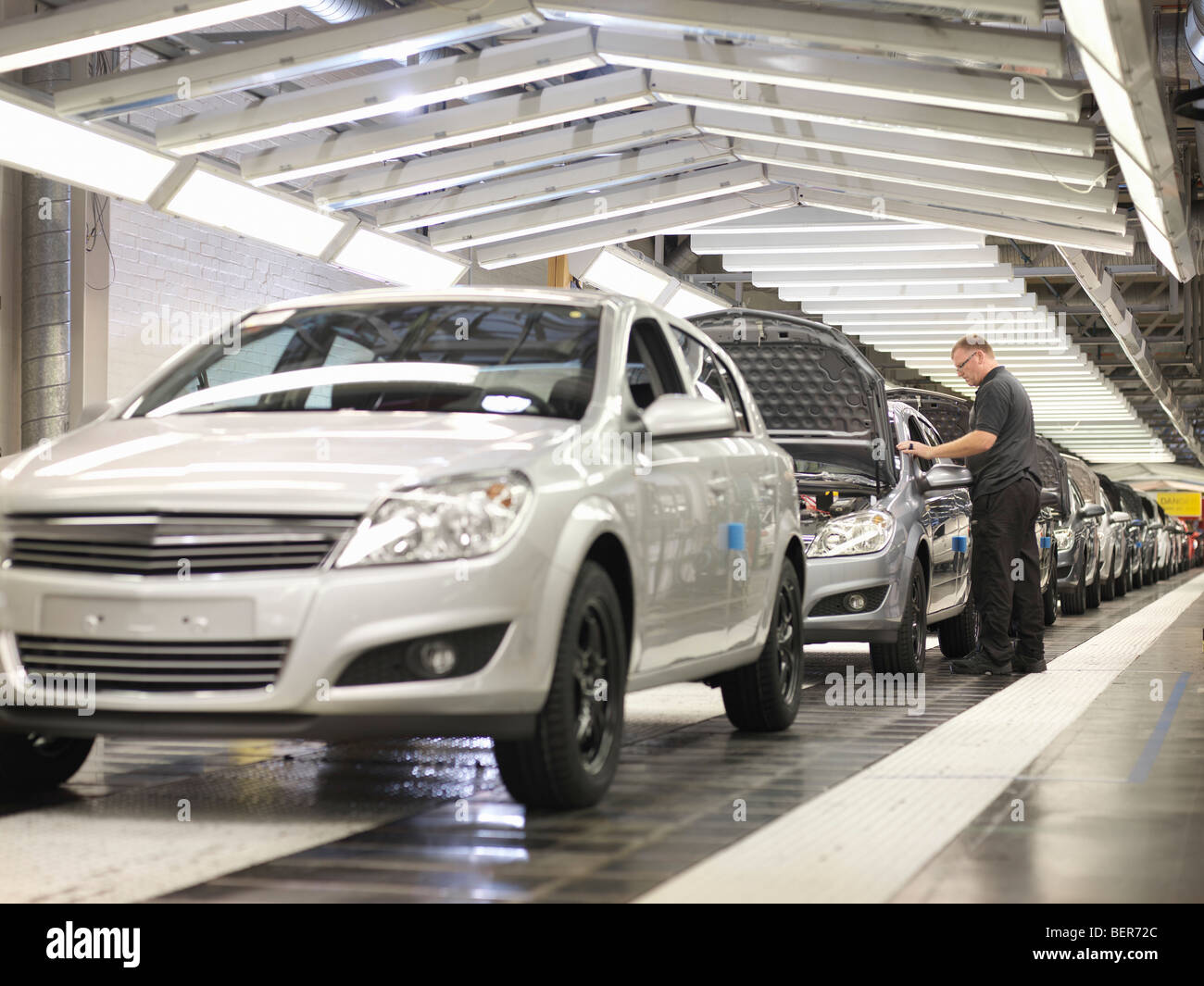 Worker Checking Cars On Production Line - Stock Image