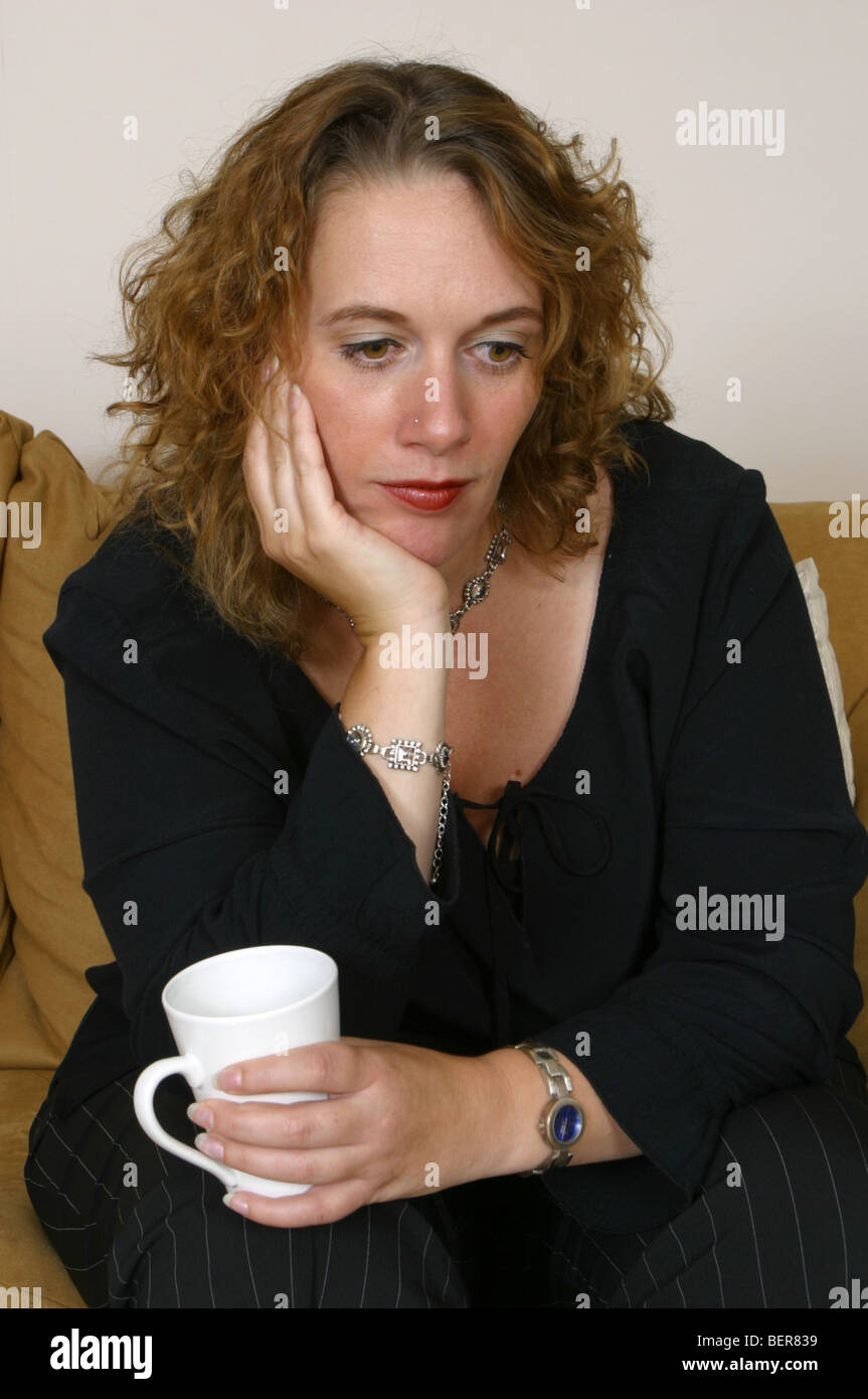 Sad depressed woman - thinking woman, 30s woman despondent - Stock Image