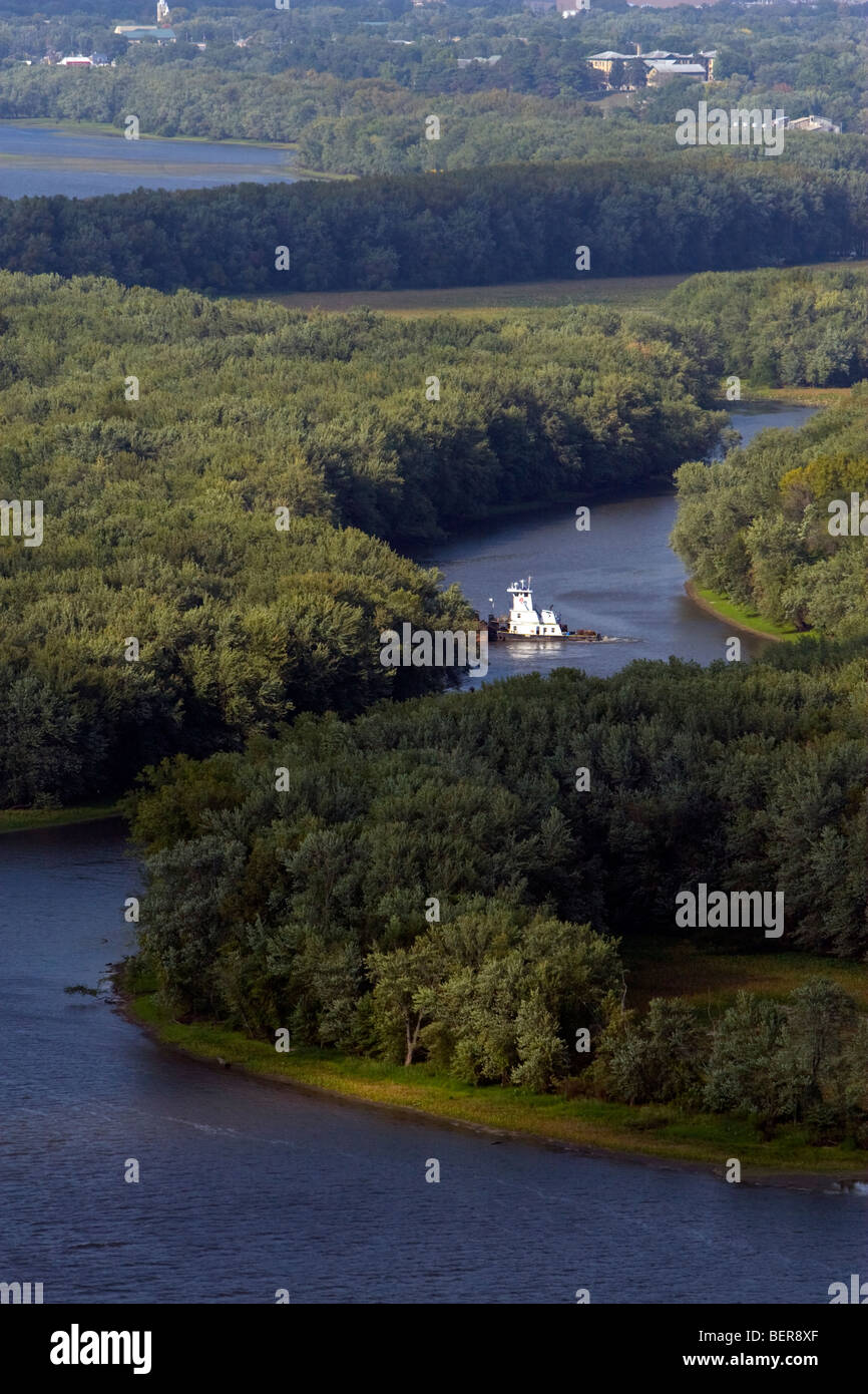 Handling a few barges in the backwater of the Mississippi River near Prairie Du Chien, WI, a towboat motors along - Stock Image